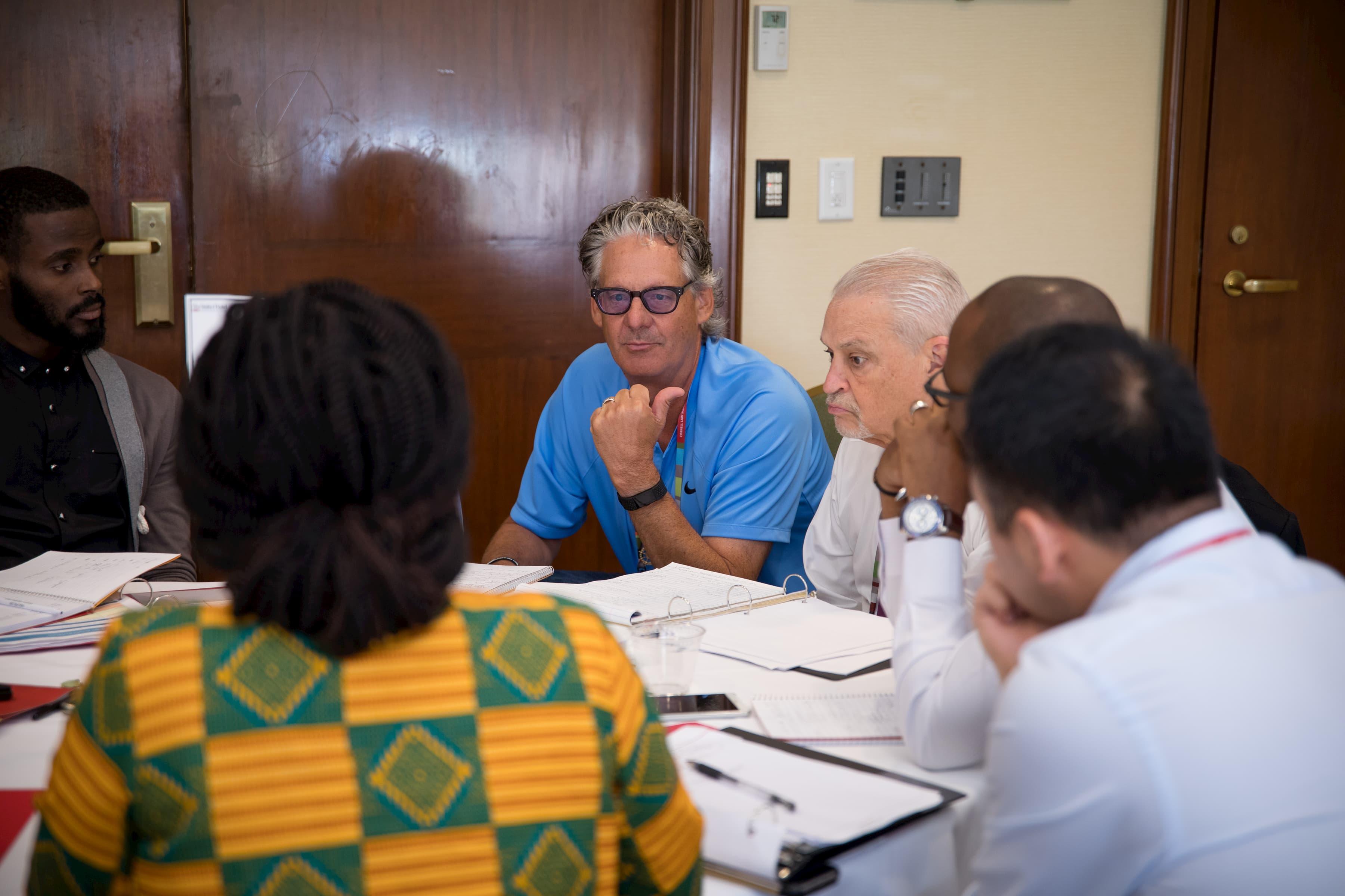 Un homme en chemise bleue est assis à une table ronde avec cinq autres personnes.