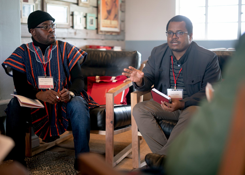 Deux hommes sont assis sur des chaises. Un homme portant une veste noire parle et l'autre homme, portant une chemise orange et noire, le regarde.