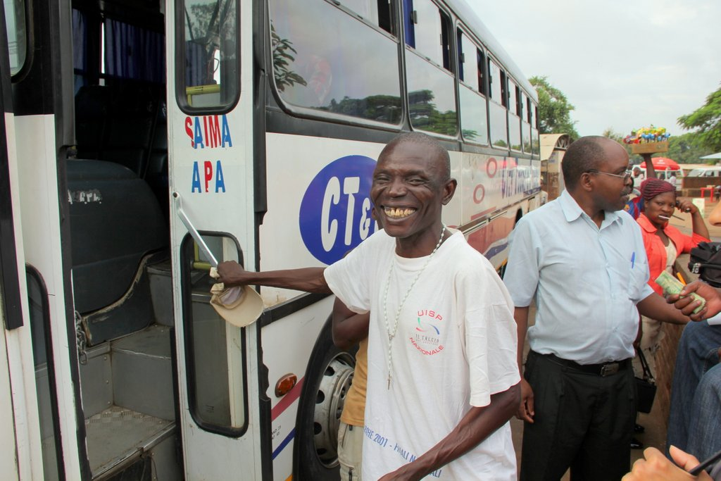 A man in a white shirt standing in front of a bus and smiling at the camera.