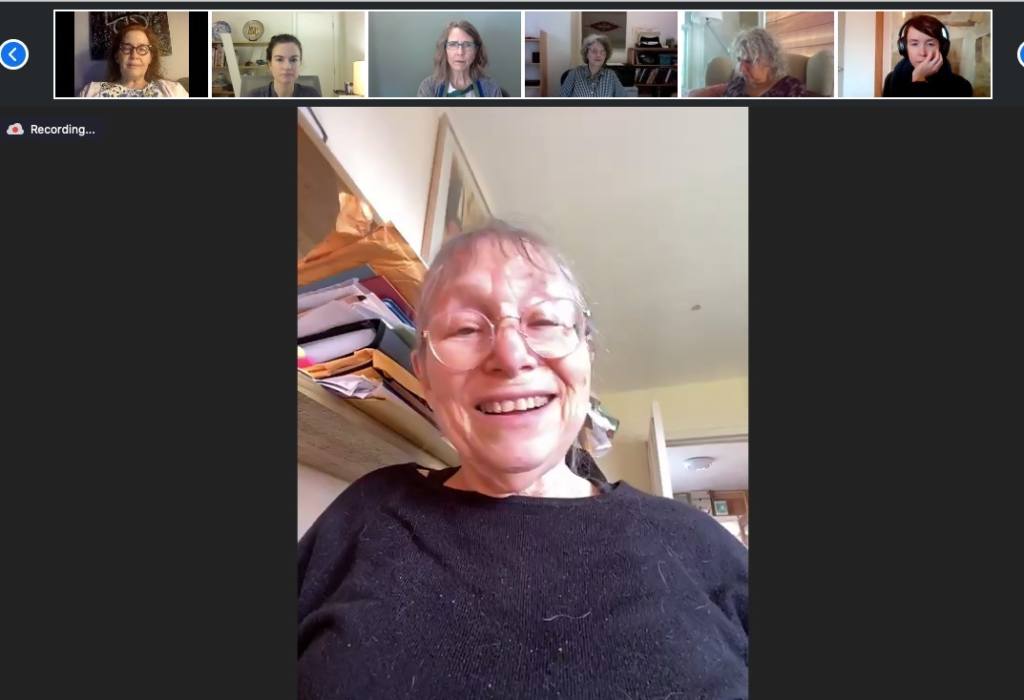 A woman wearing glasses and a gray shirt speaks during a video conference. Six people, their pictures smaller, listen.